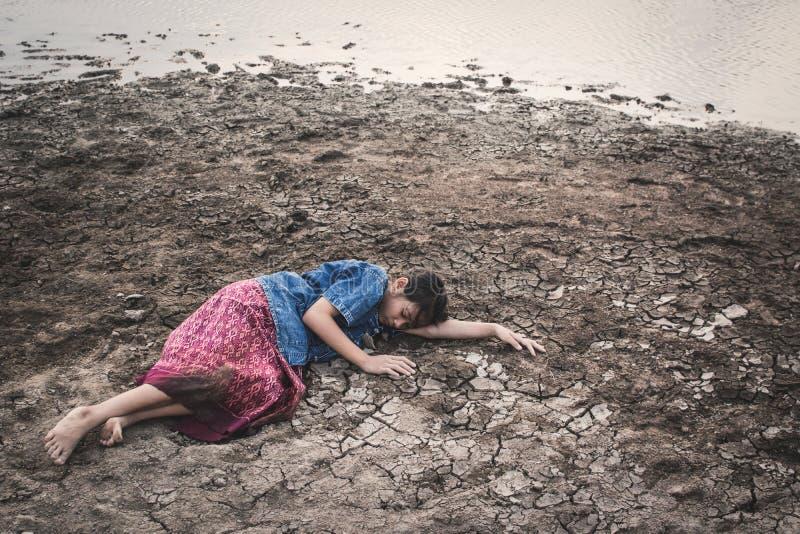 Ragazza triste stanca ed esaurita su terra asciutta incrinata immagini stock libere da diritti