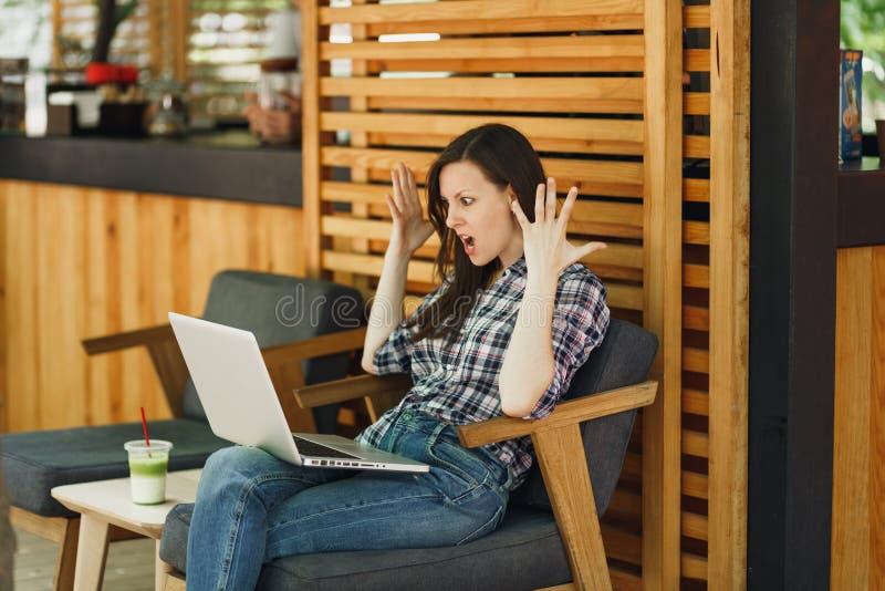 Ragazza turbata triste di grido arrabbiata in caffè di legno della caffetteria della via di aria aperta che si siede con il compu immagini stock