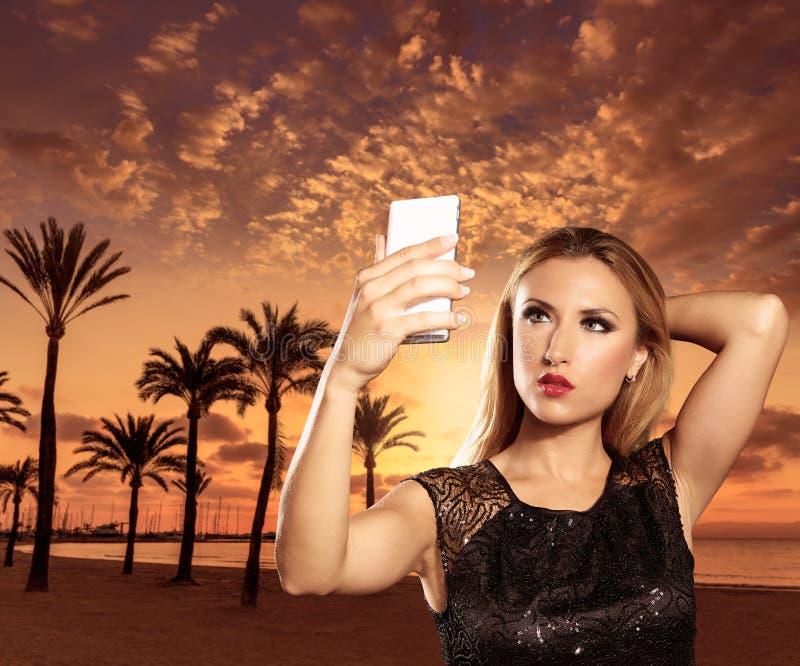 Ragazza turistica bionda che prende le foto del tramonto di Mallorca fotografia stock