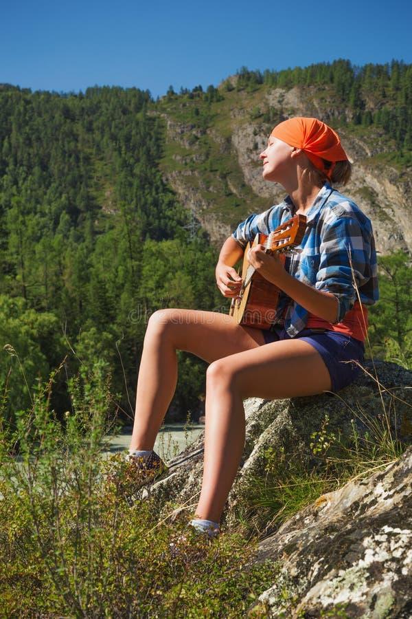 Ragazza turistica che gioca una chitarra immagini stock