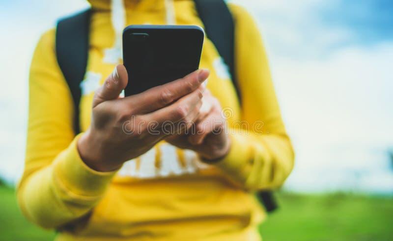 Ragazza turistica sull'erba verde del fondo facendo uso del primo piano mobile dello smartphone, donne che tengono nella tecnolog immagini stock libere da diritti
