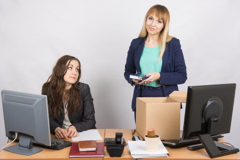Ragazza in ufficio che sta con un sorriso davanti ad una scatola circa i colleghi immagini stock