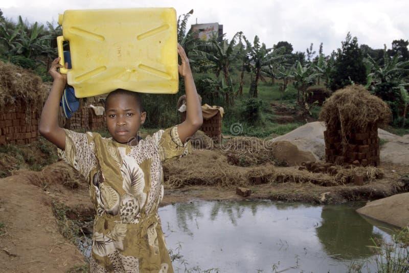 Ragazza ugandese all'acqua potabile di trasporto del pozzo fotografia stock libera da diritti