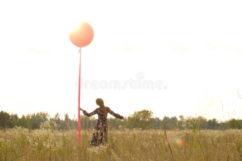 Ragazza in un bello vestito con i fiori con un pallone rosso su un guinzaglio nel campo al tramonto fotografia stock