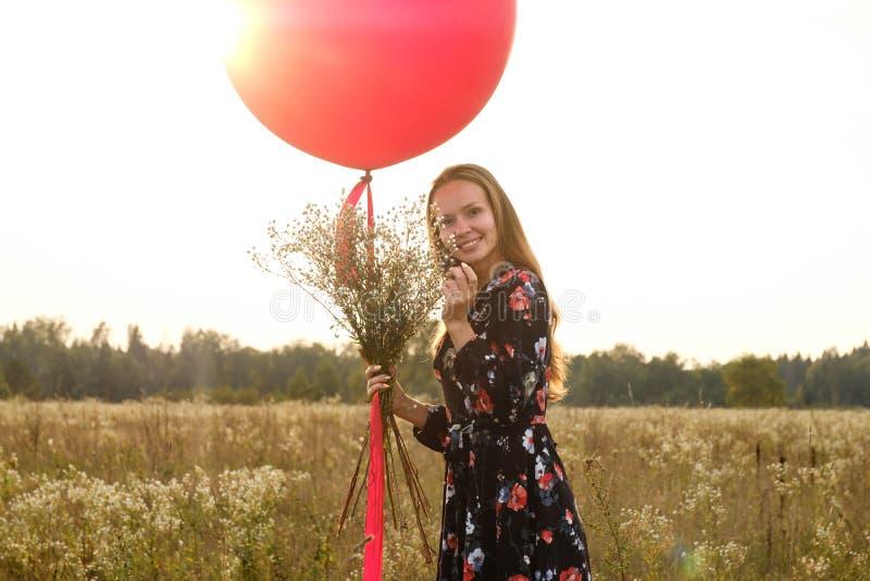 Ragazza in un bello vestito con i fiori con un pallone rosso su un guinzaglio nel campo al tramonto fotografie stock