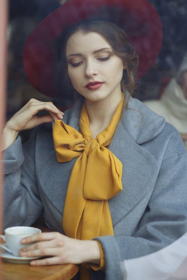 Ragazza in un caffè con una tazza di caffè e un cappello orologio attraverso il vetro di una ragazza che si siede in un caffè Bel fotografia stock