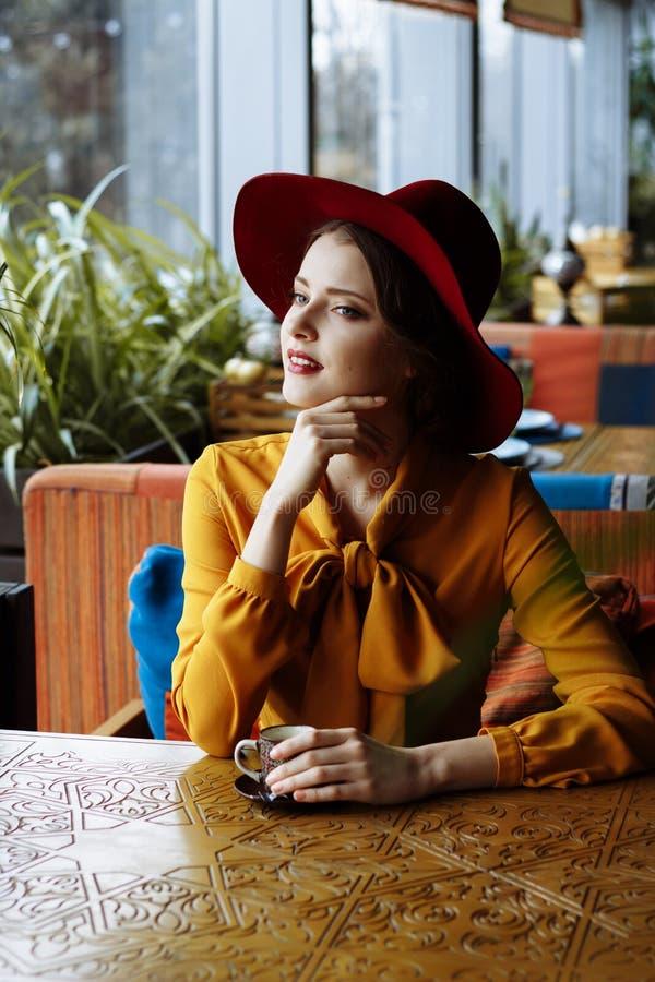 Ragazza in un caffè con una tazza di caffè e un cappello Ritratto della ragazza sensuale che porta cappello e blusa flosci con l' fotografie stock