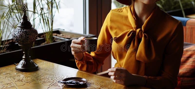 Ragazza in un caffè con una tazza di caffè e un cappello Ritratto della ragazza sensuale che porta cappello e blusa flosci con l' fotografia stock