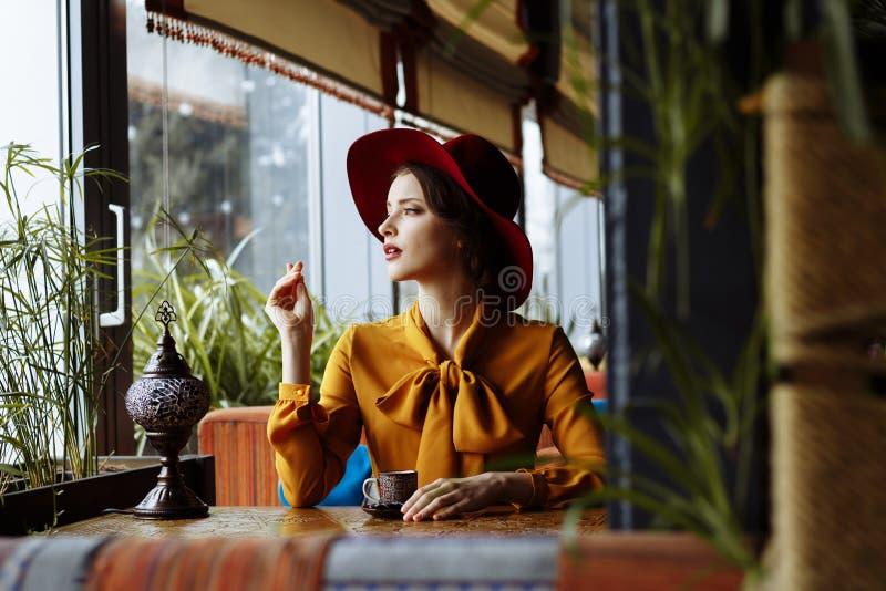 Ragazza in un caffè con una tazza di caffè e un cappello Ritratto della ragazza sensuale che porta cappello e blusa flosci con l' fotografie stock libere da diritti