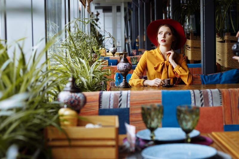 Ragazza in un caffè con una tazza di caffè e un cappello Ritratto della ragazza sensuale che porta cappello e blusa flosci con l' immagini stock libere da diritti