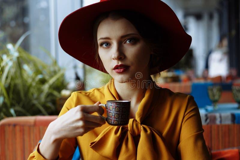 Ragazza in un caffè con una tazza di caffè e un cappello Ritratto della ragazza sensuale che porta cappello e blusa flosci con l' immagine stock libera da diritti