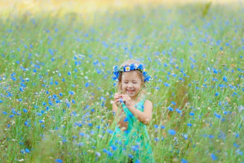Ragazza in un campo che tiene un mazzo dei fiori blu fotografie stock