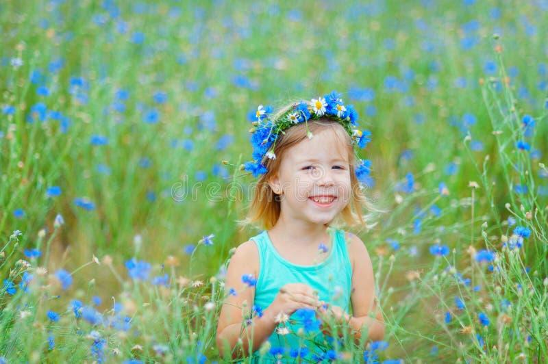Ragazza in un campo che tiene un mazzo dei fiori blu fotografie stock libere da diritti