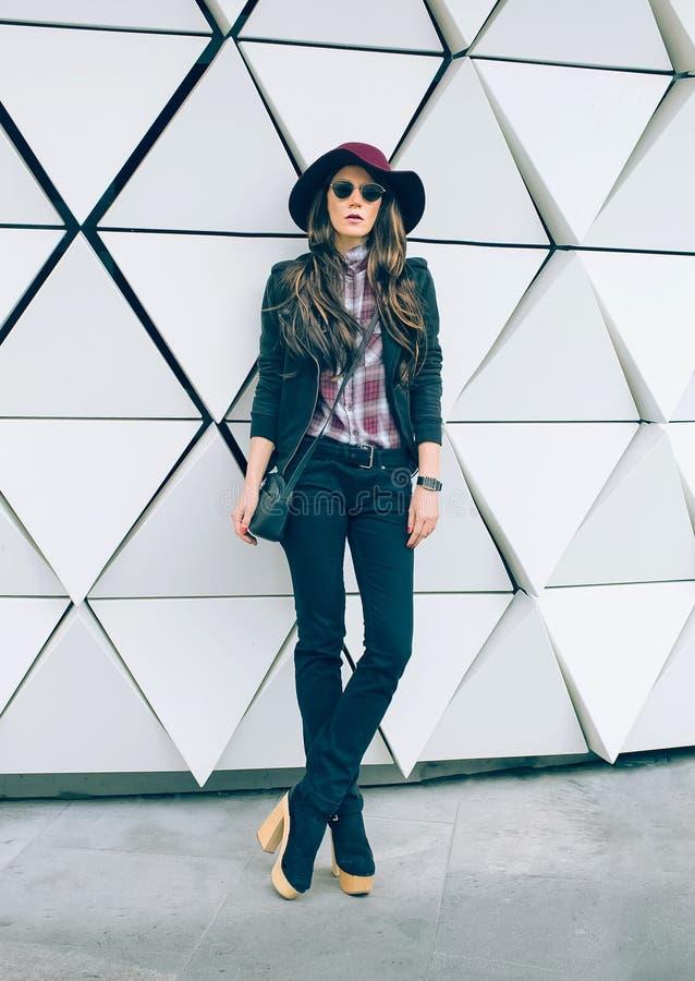 Ragazza in un cappello alla moda su una via della città Stile di modo fotografie stock libere da diritti