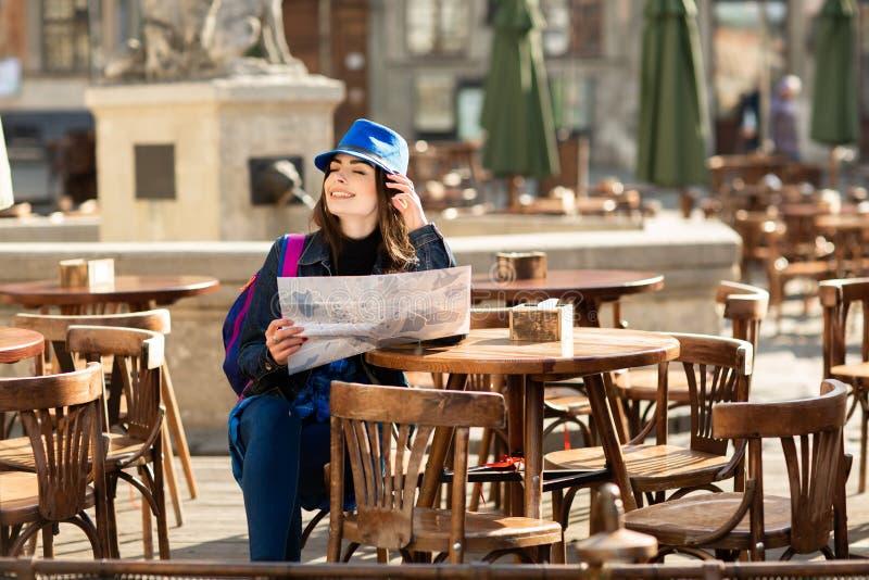 Ragazza in un cappello blu che riposa sul terrazzo di estate nella vecchia città ed esaminante la mappa Leopoli, Ucraina fotografia stock