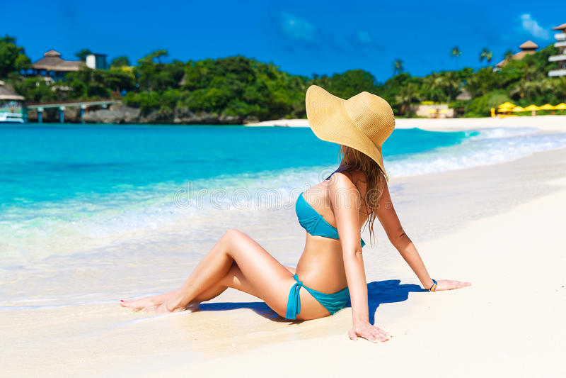 Ragazza in un cappello di paglia su una spiaggia tropicale Vacanza di estate fotografie stock