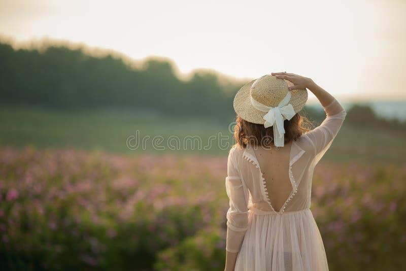 Ragazza in un cappello e uno sguardo beige del vestito al giacimento di fiore fotografie stock libere da diritti
