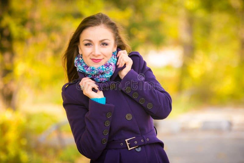 Ragazza in un cappotto blu scuro contro fondo delle foglie di autunno fotografie stock libere da diritti