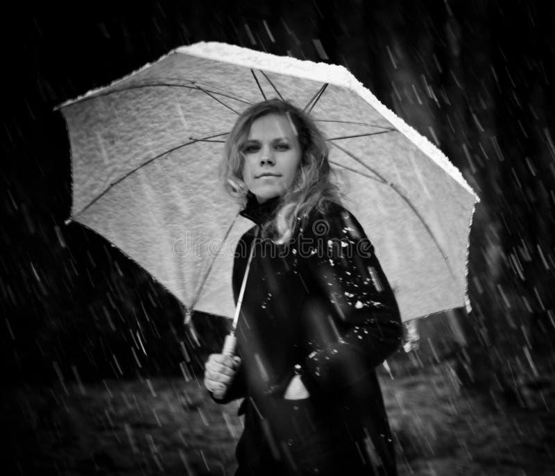 Ragazza in un cappotto nero ed in un ombrello bianco che cammina giù la via molto in una forte nevicata fotografia stock