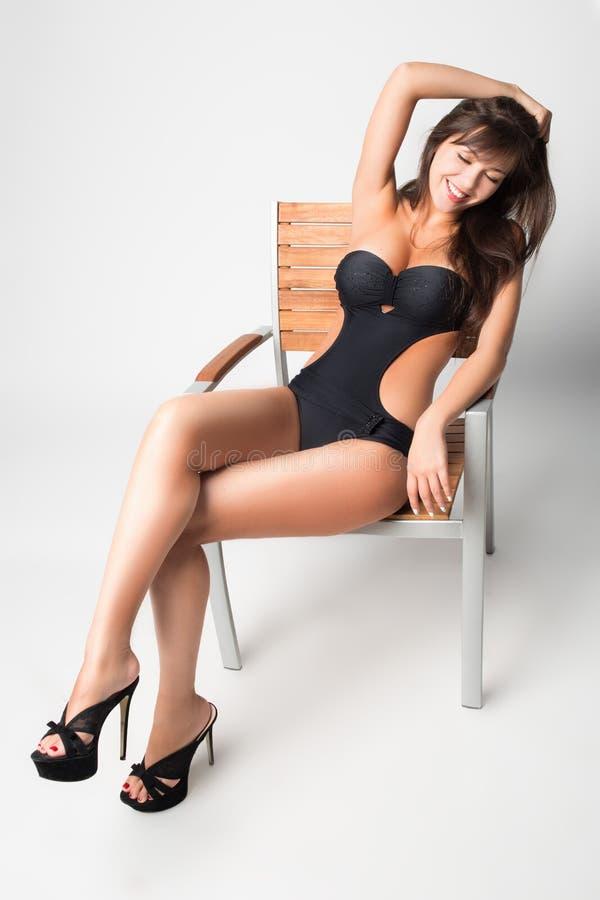 Ragazza in un costume da bagno. sedendosi su una sedia. fotografie stock libere da diritti