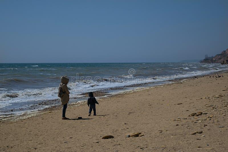 Ragazza in un impermeabile beige che cammina con un piccolo figlio immagini stock libere da diritti