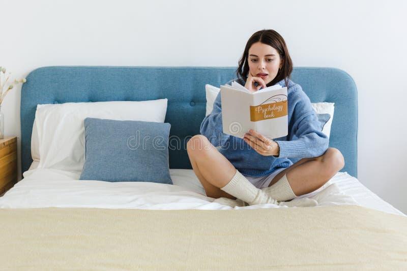 Ragazza in un maglione blu che legge un libro sulla psicologia che si siede sul letto in un interno accogliente immagine stock