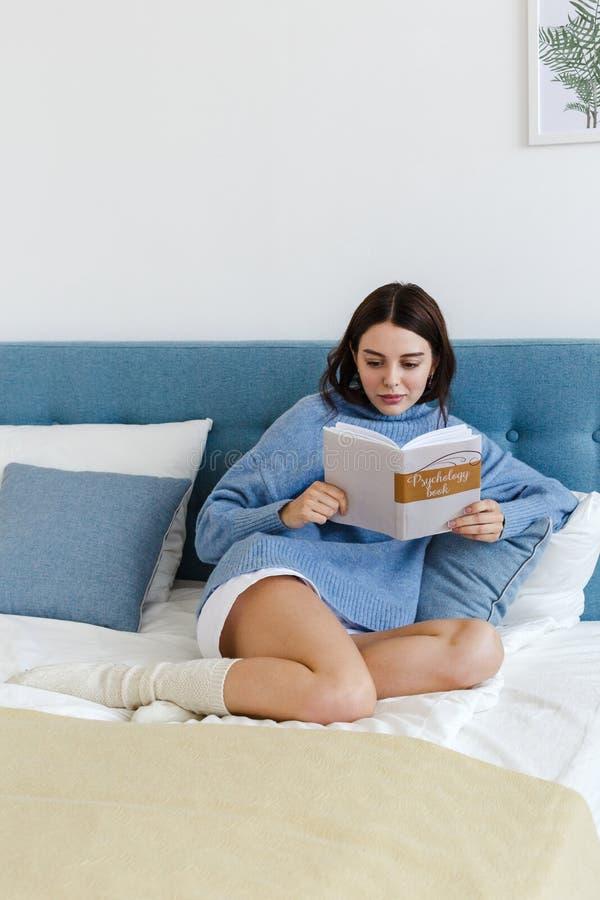 Ragazza in un maglione blu che legge un libro sulla psicologia che si siede sul letto in un interno accogliente immagini stock libere da diritti