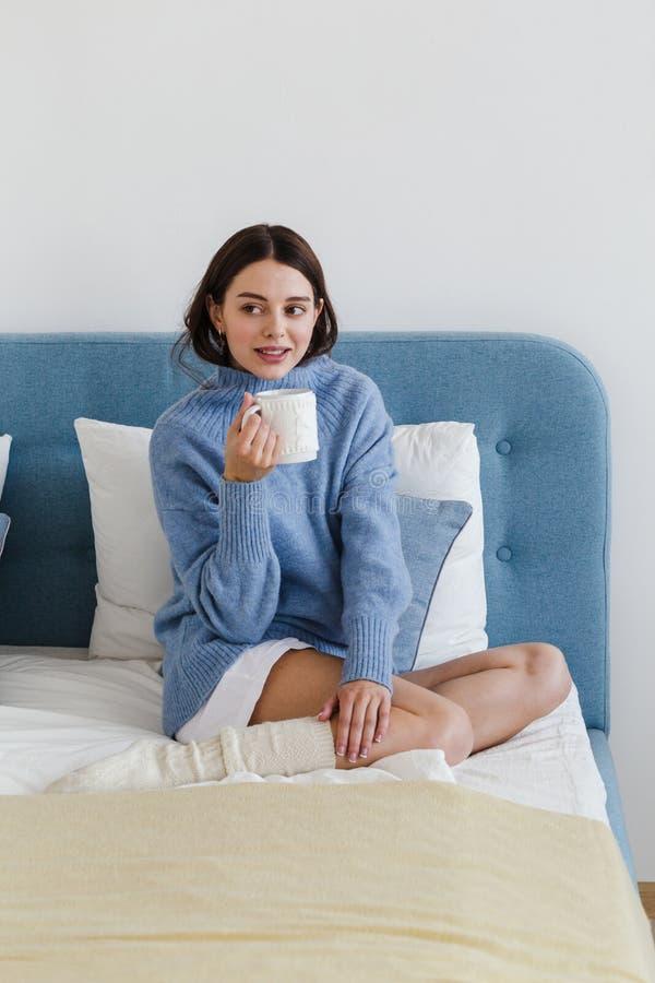 Ragazza in un maglione blu nell'interno di stile del hygge con una tazza di tè che caldo la sua mano si siede sul letto fotografia stock
