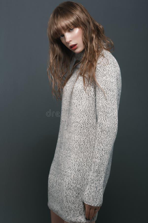 Ragazza in un maglione nello studio fotografia stock libera da diritti