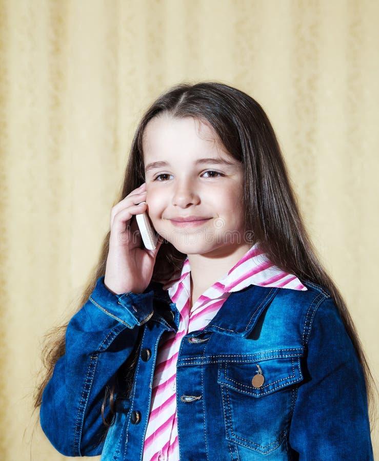 Ragazza in un rivestimento blu del denim che parla su un telefono