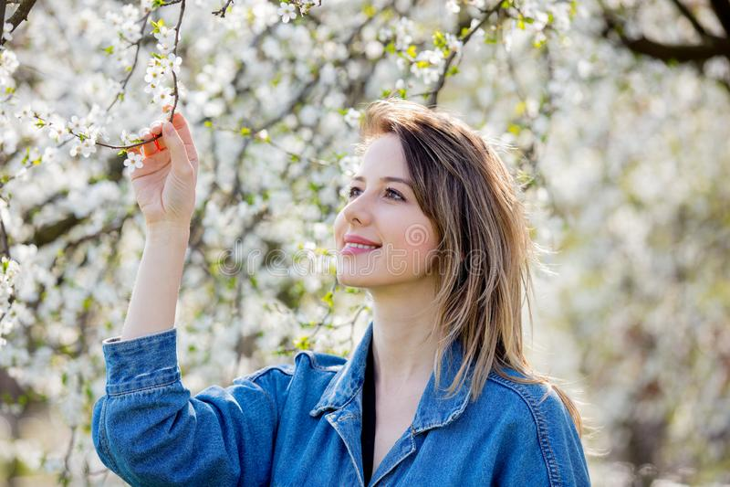 Ragazza in un soggiorno del rivestimento del denim vicino ad un albero di fioritura fotografie stock