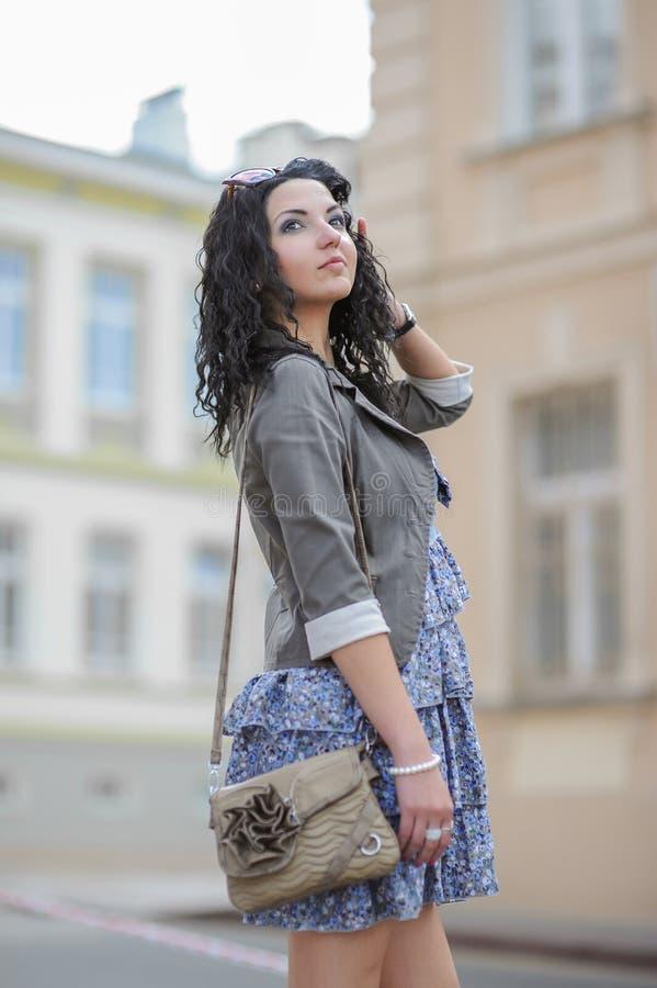 Ragazza in un vestito blu che cammina nella città Giovane donna che posa in un vestito blu nella vecchia città fotografia stock