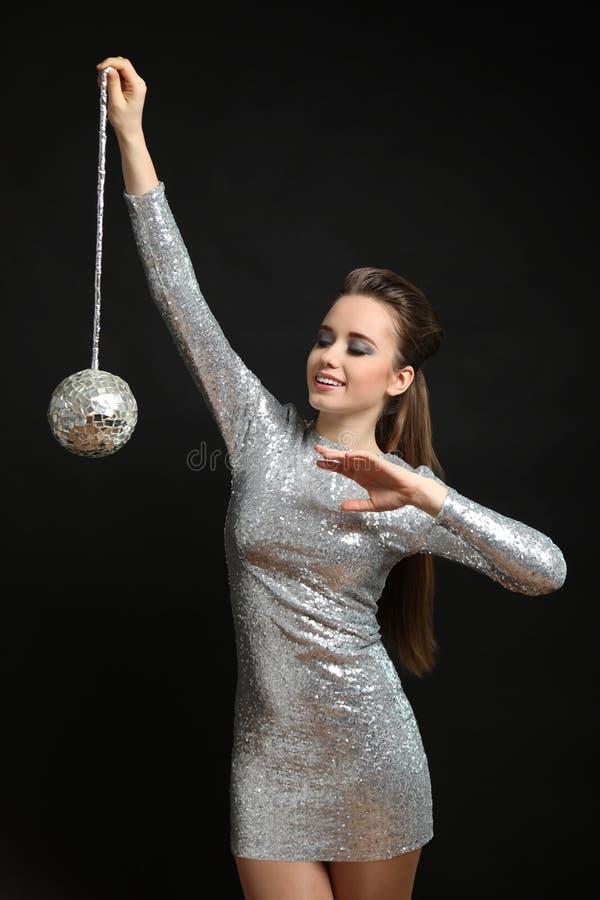 Ragazza in un vestito d'argento con una palla della discoteca immagini stock libere da diritti