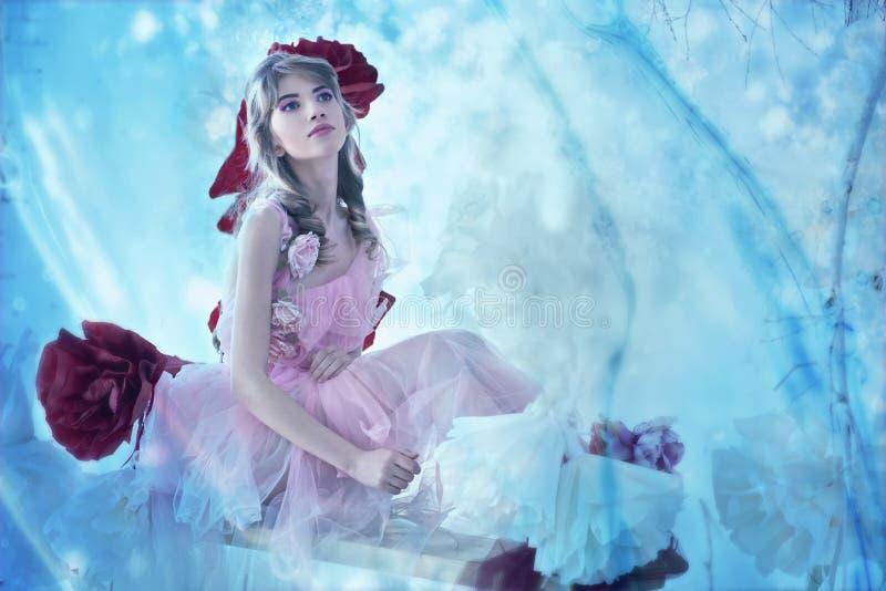 Ragazza in un vestito delicatamente rosa in uno studio interno fotografia stock