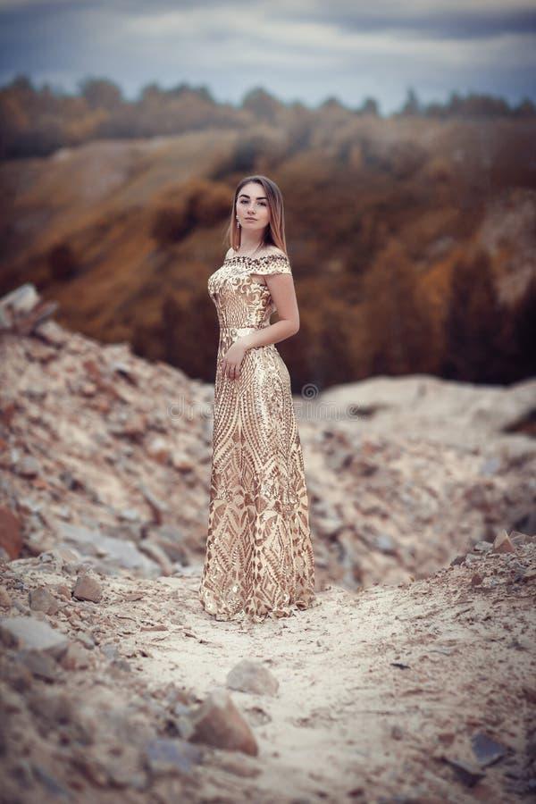 Ragazza in un vestito dorato su un fondo delle rocce fotografia stock
