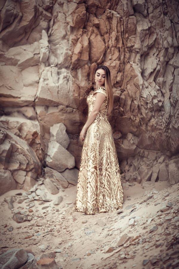 Ragazza in un vestito dorato su un fondo delle rocce immagini stock