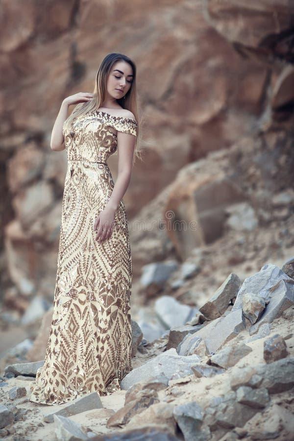 Ragazza in un vestito dorato su un fondo delle rocce immagini stock libere da diritti