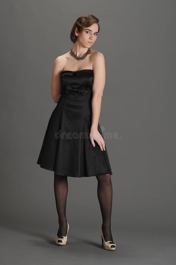 Ragazza in un vestito nero immagini stock