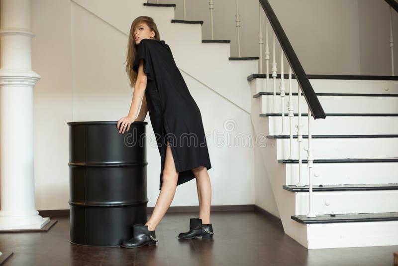 Ragazza in un vestito nero che sta accanto al nero in avvitamento immagini stock