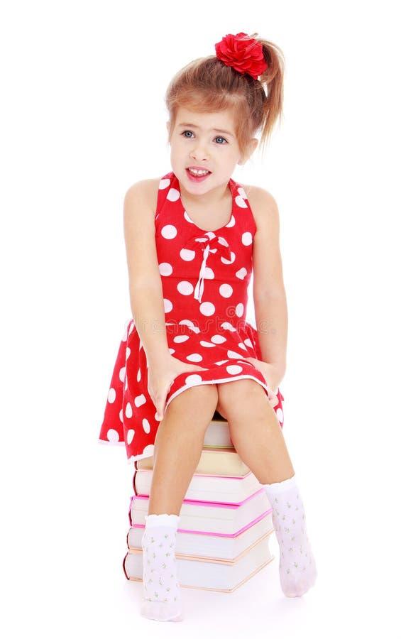 Ragazza in un vestito rosso con i pois che si siedono sopra fotografia stock