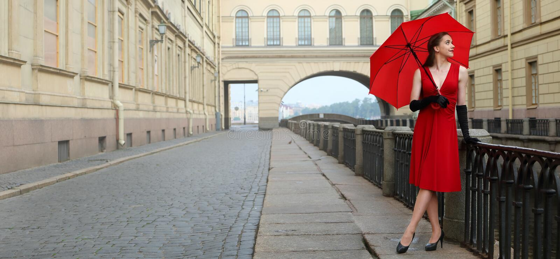 Ragazza in un vestito rosso sui precedenti della scanalatura di inverno a St Petersburg immagini stock libere da diritti
