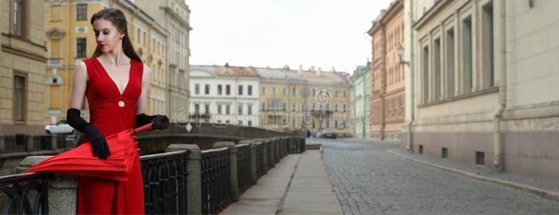 Ragazza in un vestito rosso sui precedenti della scanalatura di inverno a St Petersburg fotografia stock