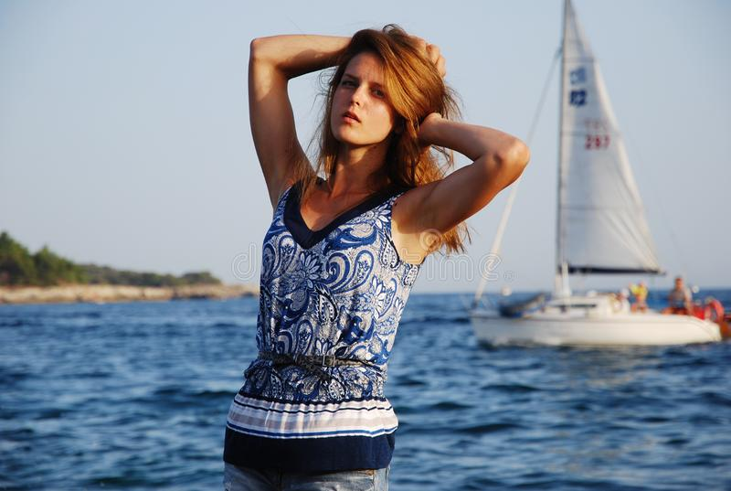 Ragazza in una maglietta e pantaloncini corti sulla costa prima del tramonto fotografie stock libere da diritti