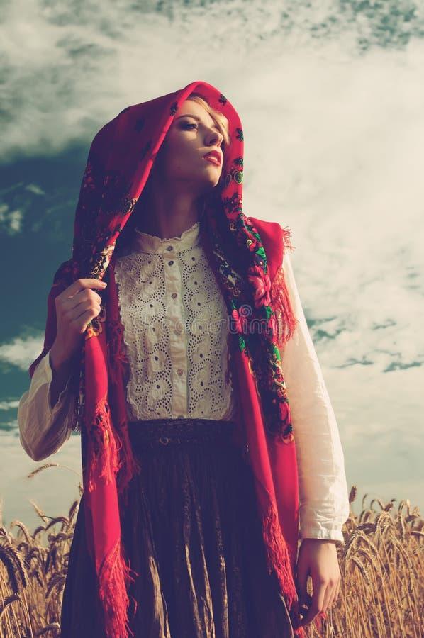 Ragazza in una sciarpa rossa nel campo fotografia stock libera da diritti