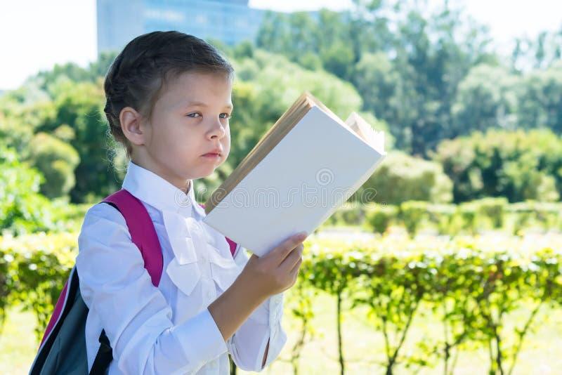 Ragazza in uniforme scolastico che legge un libro nella via in buon tempo fotografie stock