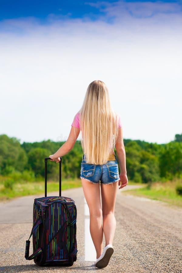 Ragazza in valigia della strada, maglietta rosa, shorts blu, altezza completa, b fotografie stock