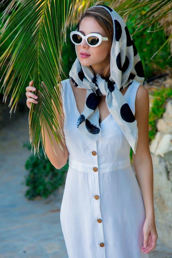 Ragazza in vestito bianco che sta palma vicina immagine stock
