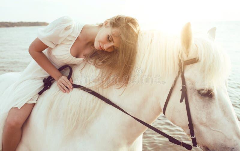 Ragazza in vestito bianco con il cavallo sulla spiaggia fotografia stock