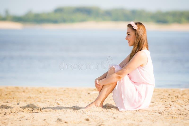 Ragazza in vestito bianco dalla luce di estate che si siede sulla spiaggia sabbiosa dal fiume immagini stock libere da diritti