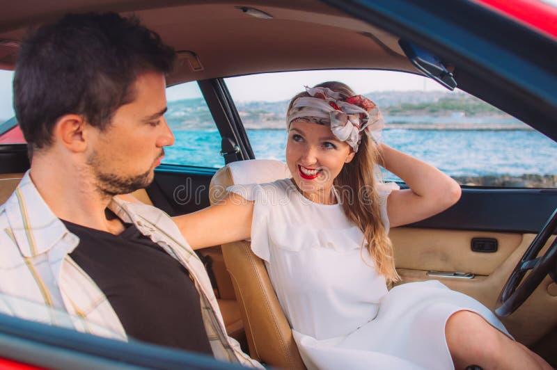Ragazza in vestito bianco ed in uomo che si siedono sui sedili anteriori dell'automobile rossa immagine stock